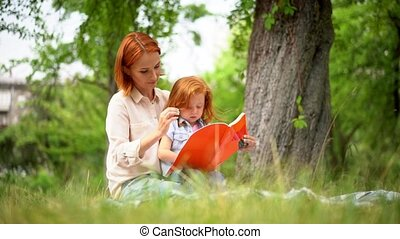Mother and girl sit under a tree reading a book - Beautiful...