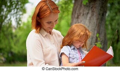 Mother and girl sit under a tree reading a book - Close Up...