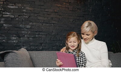 Mother and girl watching video fairytales on tablet computer...