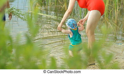 Mother and grandfather playing with baby boy in the lake. Beautiful kid walks on water