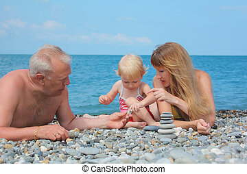 Mother and grandfather with child on sea coast and  pyramid of stones