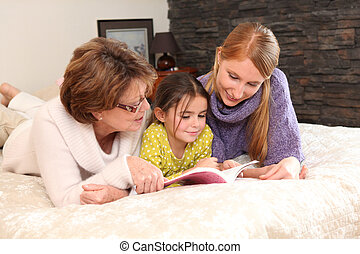 Mother and grandma reading with little girl