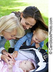 Mother and grandmother smiling at baby