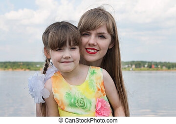 Mother and happy little daughter enjoying near river at summer day