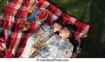mother and happy little son speak and laugh lying on grass