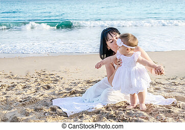 Mother and her baby girl on the sandy beach