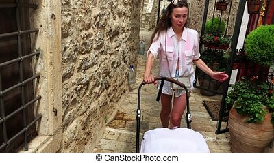 Mother and her baby traveling along narrow old town street with a stroller