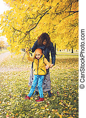 Mother and her beloved son with disability in autumn park....