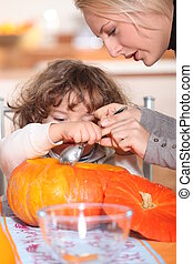 mother and her child emptying a pumpkin