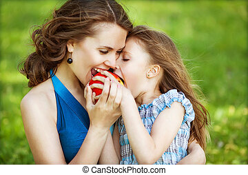 Mother and her child enjoy the early spring, eating apple,...