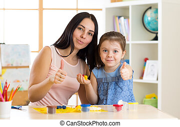 mother and her child have a fun pastime with colorful play clay toys