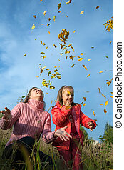 mother and her child throwing yellow maple leaves