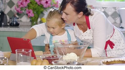 Mother and her cute young daughter in the kitchen