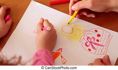 Mother and her daughter draw with colored markers, only hands are visible