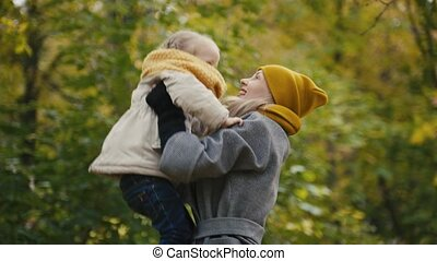 Mother and her daughter little girl playing in a autumn park - mommy throws child