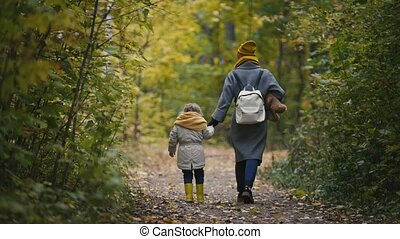 Mother and her daughter little girl walking in a autumn park - mommy, child moving away