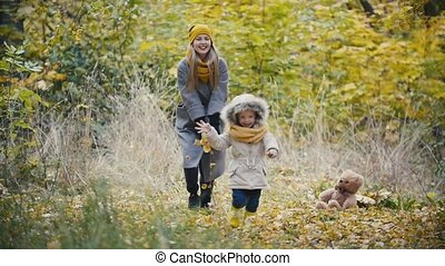 Mother and her daughter little girl walking in a autumn park - child running, slow motion