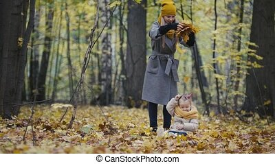 Mother and her daughter little girl walking in a autumn park - mommy and child have fun and playing with yellow leaves