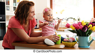 Mother and her daughter painting Easter eggs
