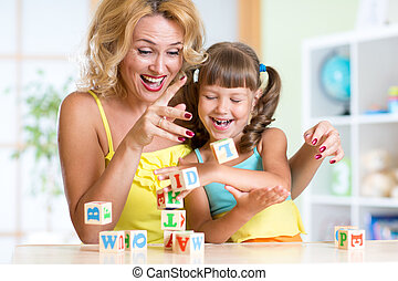 Mother and her daughter playing with cubes