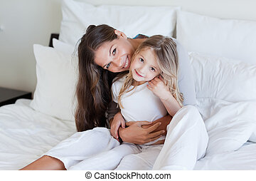 Mother and her daughter posing on a bed