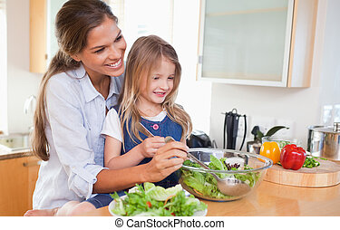 Mother and her daughter preparing a salad
