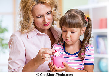 Mother and her daughter putting coins into piggy bank