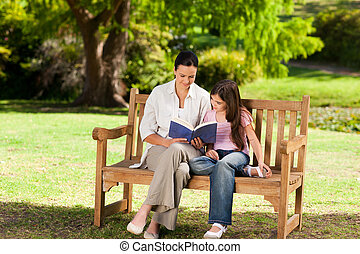 Mother and her daughter reading a b