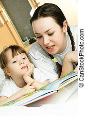 mother and her daughter reading a book