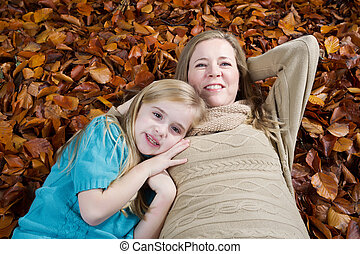 Mother and her daughter relaxing on a bed of fall leaves