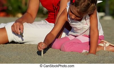Mother and her daughter sitting on sand and girl drawing on it by sticks