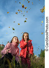 mother and her daughter throwing leaves in the air