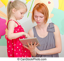 Mother and her daughter using tablet pc.