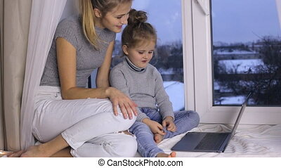 Mother and her daughter with laptop