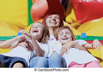 Mother and her daughters having fun on jumping castle - Mom...