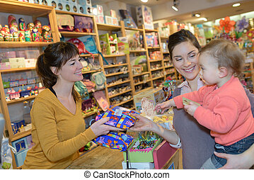 mother and her friend with child in a toy store