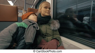 Mother and her gentle loving son traveling by train
