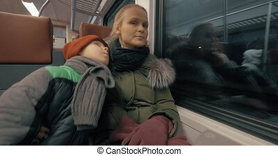 Mother and her gentle loving son traveling by train - Boy...