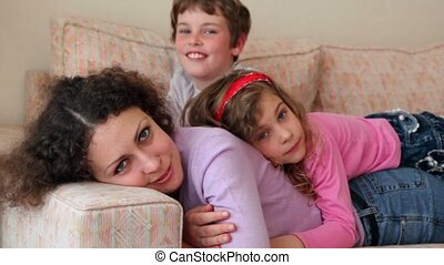 Mother and her kids boy and little girl lay on sofa