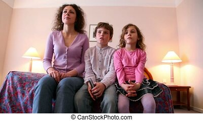 Mother and her kids boy and little girl sit on sofa and watch tv