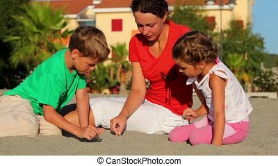 Mother and her kids sitting on sand and writing on it -...