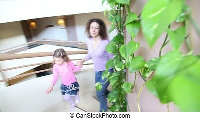 Mother and her kids walk upstairs by spiral stairway with plants on wall in multiple floor building