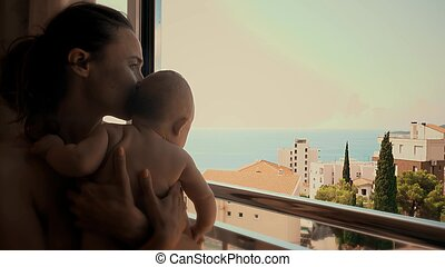 Mother and her little baby look at sea through the window on vacation