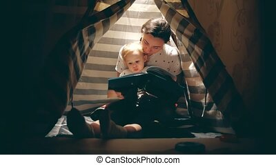 Mother and her little baby read a book together in a cozy...