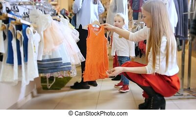 Mother and her little daughter buy a red summer dress