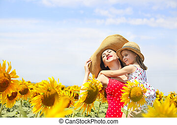 Mother and her little daughter in the sunflower field