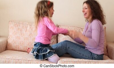 Mother and her little daughter jump on sofa with hold hands