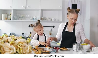 Mother and her little daughter on the kitchen decorates the dessert for breakfast