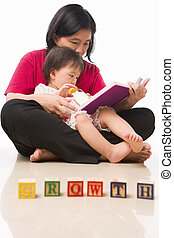 Mother and her little girl reading book