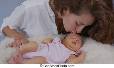 Mother and her Newborn Baby. Happy Mother holding her New born Baby girl kissing and hugging. Maternity concept. Parenthood. Motherhood. Beautiful Happy Family. Adoption. Slow motion